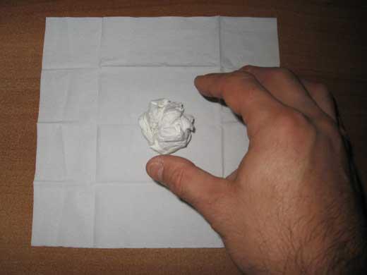 mano-che-poggia-la-pallina-di-carta-al-centro-del-fazzolettino-aperto